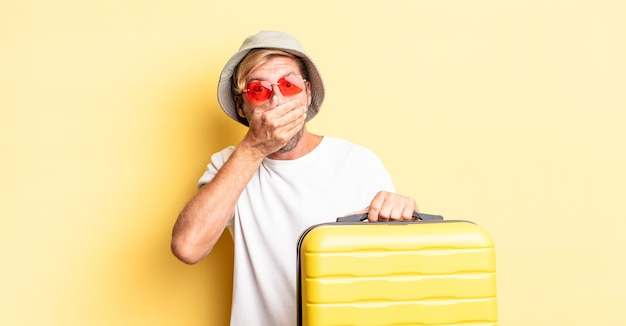 Homme adulte blond couvrant la bouche avec les mains avec un choc. concept de voyageur