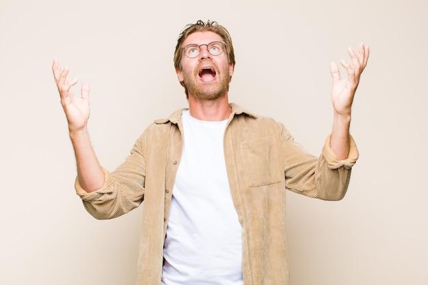 Homme adulte blond se sentir heureux, surpris, chanceux et surpris, célébrant la victoire avec les deux mains en l'air