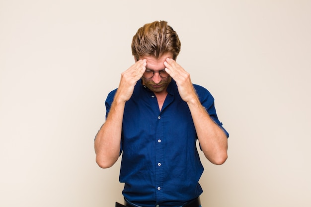Homme adulte blond à la stress et frustré, travaillant sous pression avec un mal de tête et troublé par des problèmes