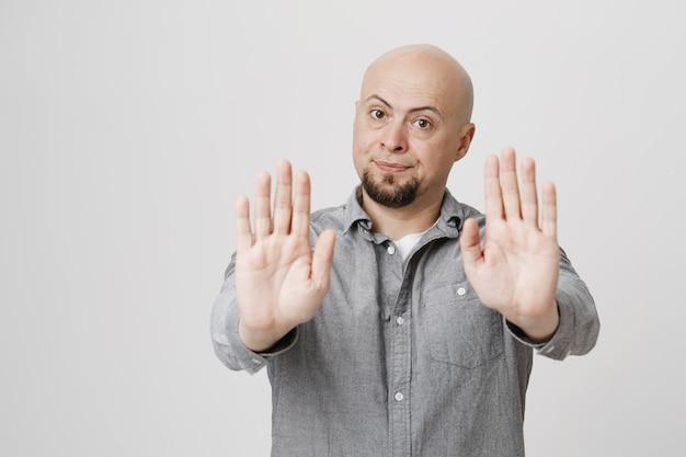 Homme adulte chauve insatisfait montrer panneau d'arrêt, interdire l'action