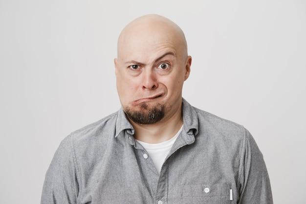 Homme adulte chauve ludique drôle plissant les yeux et grimaçant