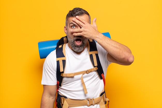 Homme adulte à choqué, effrayé ou terrifié, couvrant le visage avec la main et furtivement entre les doigts