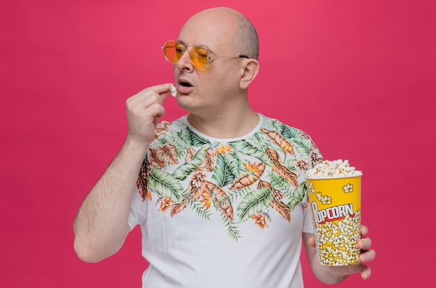 Homme adulte confiant avec des lunettes de soleil tenant un seau de pop-corn