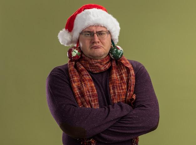 Homme adulte confiant portant des lunettes et bonnet de noel avec écharpe autour du cou debout avec une posture fermée regardant la caméra avec des boules de noël suspendues à ses oreilles isolé sur fond vert olive