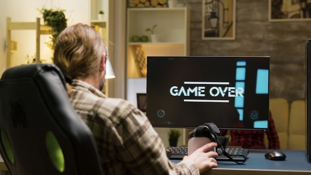 Homme adulte contrarié après avoir perdu en jouant à des jeux vidéo à l'aide d'un casque vr. jeu terminé pour le joueur masculin.