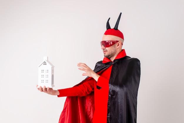 Homme adulte en costume d'halloween avec bâtiment décoratif dans ses mains