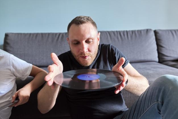 Homme adulte créatif avec disques vinyles, passe-temps et loisirs, arrière-plan à la maison