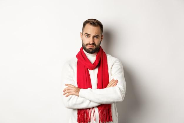 Homme adulte critique en écharpe de noël et pull à la recherche d'un appareil photo sceptique, n'aime pas quelque chose, debout sur fond blanc.