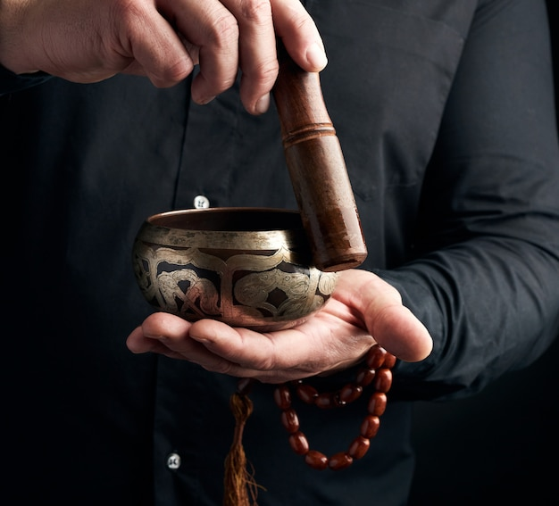Un homme adulte dans une chemise noire fait tourner un bâton en bois autour d'un bol d'eau tibétain en cuivre. rituel de méditation