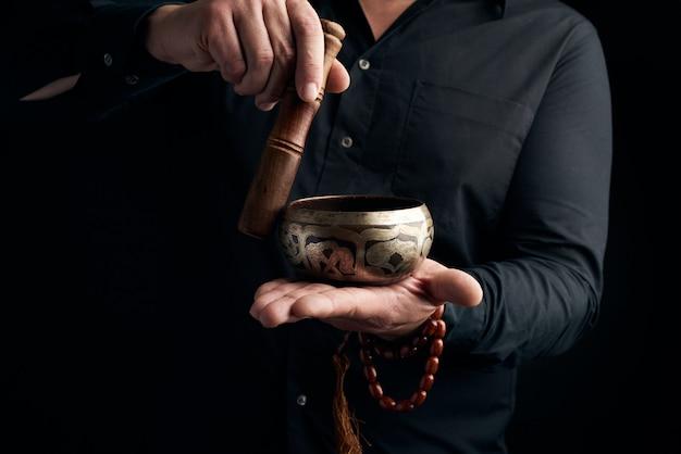 Homme adulte dans une chemise noire tourne un bâton en bois autour d'un bol d'eau tibétain en cuivre