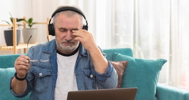 Un homme adulte dans des écouteurs sans fil est assis devant un ordinateur portable et se frotte les yeux après une dure journée de travail.