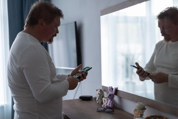 Un homme adulte devant le miroir de la chambre se regarde le matin et vérifie les nouvelles sur son smartphone