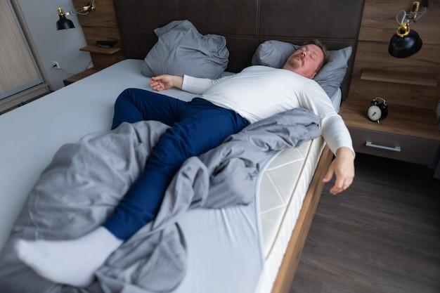 Homme adulte dormant dans la chambre sur le lit dans une pose drôle seul à la maison