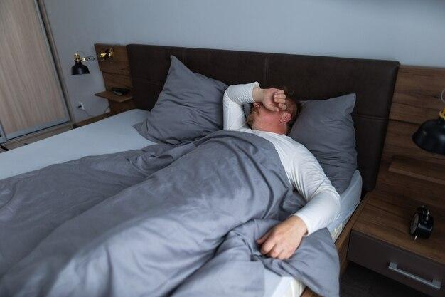 Homme adulte dormant dans la chambre sur le lit seul à la maison