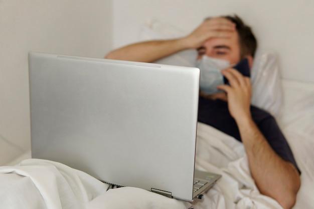 Un homme adulte est allongé dans un lit d'hôpital avec un ordinateur portable tenant sa tête. concept de travail à distance pendant la pandémie de coronavirus