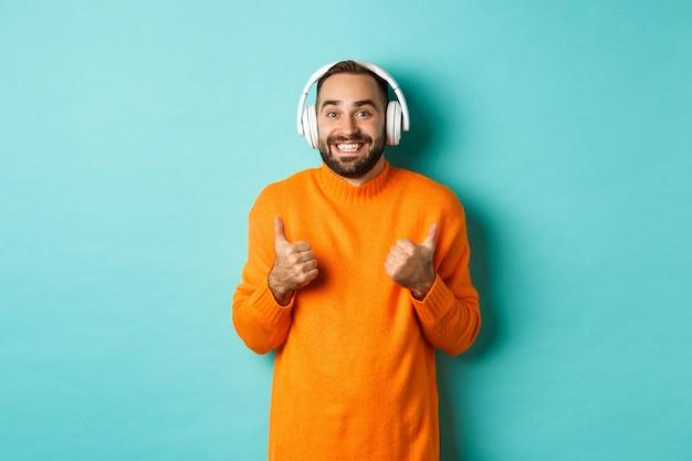 Homme adulte étonné, écouter de la musique dans les écouteurs, regardant la caméra impressionné et montrant le pouce en l'air