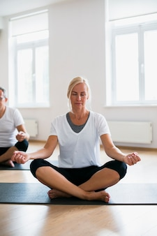 Homme adulte et femme faisant du yoga ensemble