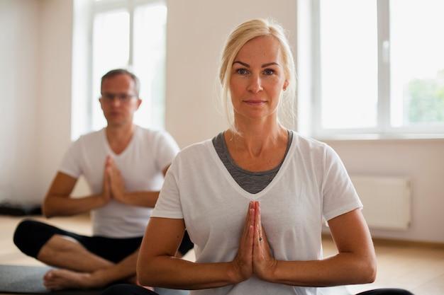 Homme adulte et femme faisant du yoga