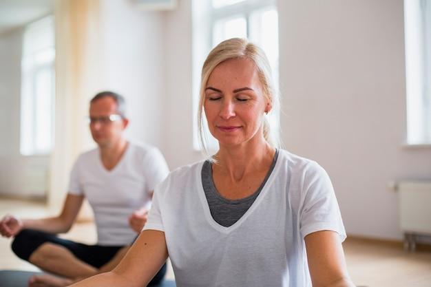 Homme adulte et femme pratiquant le yoga