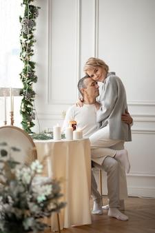 Homme adulte et femme s'embrassant près de la table de fête dans le hall