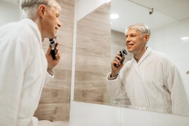 Homme adulte gai se rase au miroir dans la salle de bain