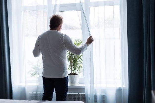 Un homme adulte à la grande fenêtre de la chambre s'étire le matin après avoir dormi