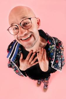 Homme adulte avec une grimace souriante et regardant la caméra sur fond de studio rose.
