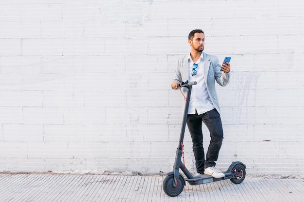 Homme adulte latine avec des lunettes de soleil, bien habillé et scooter électrique parlant sur son téléphone portable assis dans la rue avec un fond de mur blanc