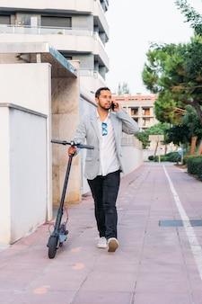 Homme adulte latine avec lunettes de soleil, scooter bien habillé et électrique parlant sur son téléphone portable dans la rue
