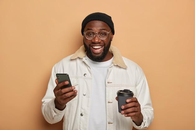 Homme adulte mal rasé noir en tenue élégante, utilise un smartphone moderne pour discuter en ligne