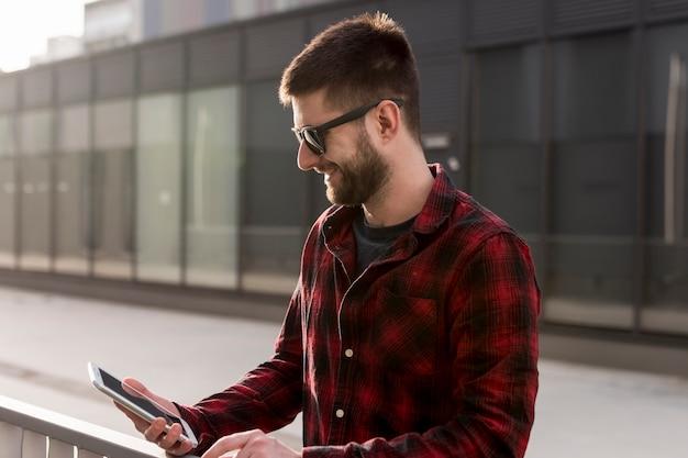 Homme adulte marchant et utilisant un téléphone portable