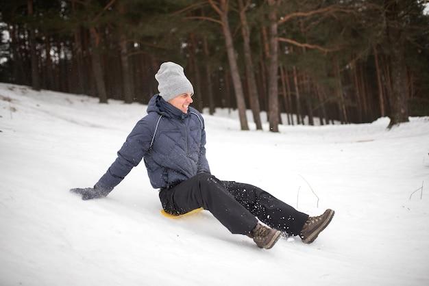 L'homme adulte monte sur la glace d'un traîneau depuis une montagne escarpée. plaisir d'hiver. pour n'importe quel but.