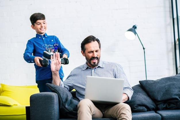 Homme adulte occupé s'asseyant sur le sofa tandis que son fils demande son aide