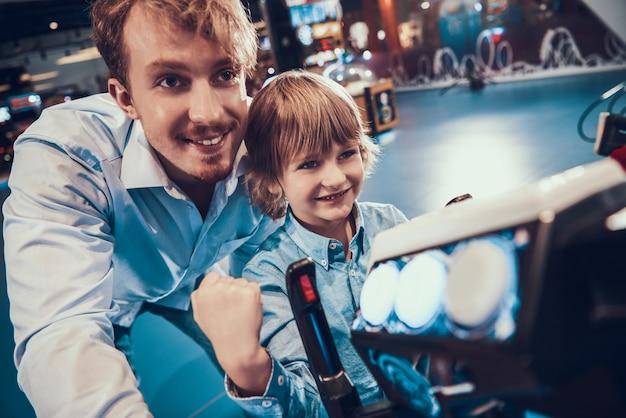 Homme adulte et petit garçon jouant à la machine de jeu