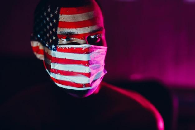 Homme adulte portant un masque médical avec le drapeau américain sur son visage dans l'obscurité.