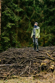 Homme adulte posant sur les bâtons dans la forêt