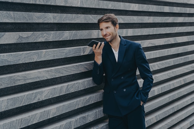 Un homme adulte professionnel prospère avec du chaume utilise un haut-parleur pour répondre à un appel entrant