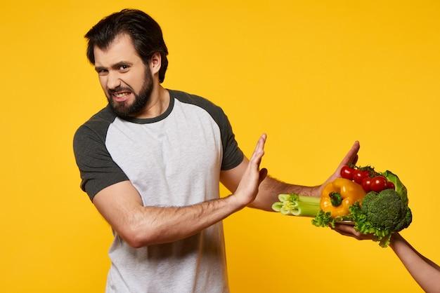 Un homme adulte refuse de manger des légumes à la main.