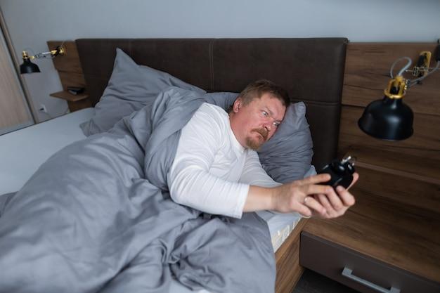 Un homme adulte se réveille au réveil sur le lit dans la chambre à la maison et est très surpris et contrarié d'avoir dormi trop longtemps