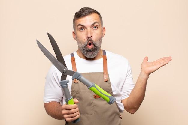 Homme adulte semblant surpris et choqué, avec la mâchoire tombée tenant un objet avec une main ouverte sur le côté
