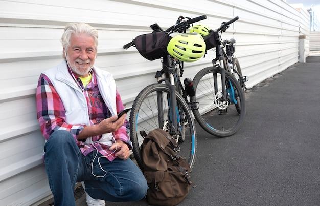 Un homme adulte senior heureux arrête de faire du vélo électrique et se repose contre un mur blanc en écoutant un téléphone portable. un peuple avec des cheveux blancs et des vêtements décontractés