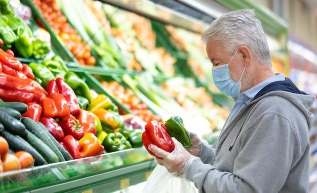 Homme adulte senior avec masque chirurgical en raison d'un coronavirus lors de ses achats au supermarché.