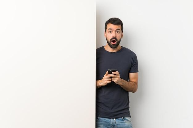 Homme adulte avec son portable et avec une expression surprise