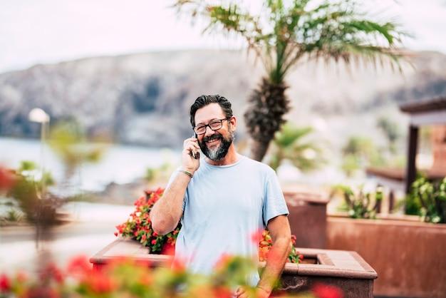 Homme adulte souriant parlant au téléphone en plein air à la maison