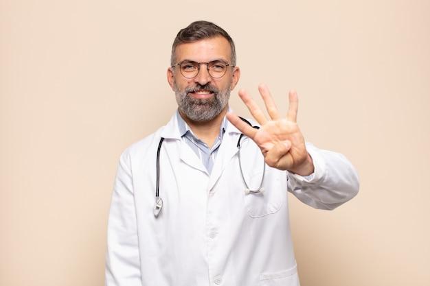 Homme adulte souriant et à la sympathique, montrant le numéro quatre ou quatrième avec la main en avant, compte à rebours
