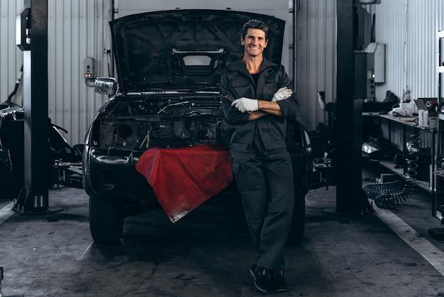 Homme adulte souriant en uniforme de travail posant debout près de la voiture ouverte noire dans le grand garage de voitures. concept de contrôle de voiture