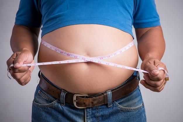 Homme adulte en surpoids ou gros en jeans très serrés avec ruban à mesurer