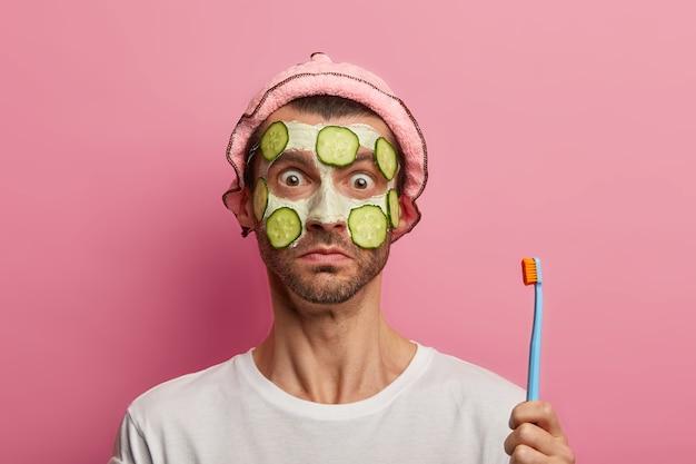 Un homme adulte surpris se soucie de la peau, applique un masque facial et des tranches de concombre, tient une brosse à dents