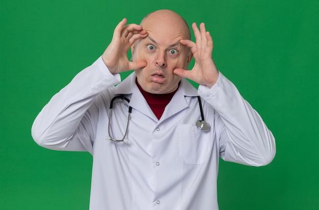 Homme adulte surpris en uniforme de médecin avec stéthoscope ouvrant les yeux avec les mains et regardant