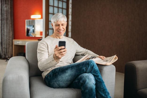 Homme adulte avec téléphone et journal assis sur un canapé à la maison. personne de sexe masculin mature en jeans se détendre dans un fauteuil